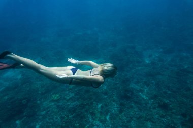 side view of woman in bikini and fins diving in ocean alone