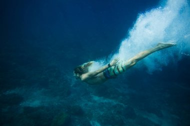 underwater pic of young man diving in ocean alone