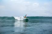 Fotografie sportliche junge Frau in sportlicher Badeanzug Reiten Surfbrett im Ozean während der Sommerferien