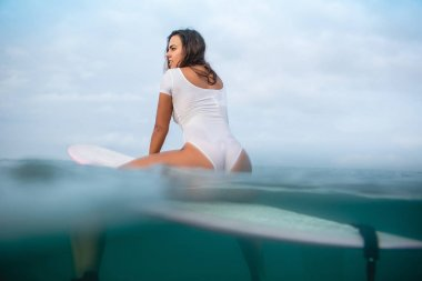 beautiful young woman in wet white swimsuit sitting on surfboard in ocean