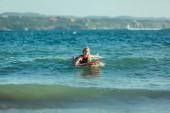 Fotografie krásné sportovkyně plavání na surfovací prkno ve vodě