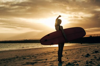 silhouette of female surfer posing with surfboard at sunset with backlit