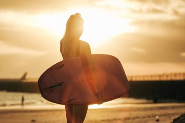 rear view of surfer posing with surfboard on beach at sunset with backlit
