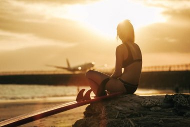 girl sitting on rock with surfboard on beach at sunset with airplane in sky