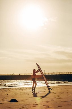 female surfer posing with surfboard on beach at sunset