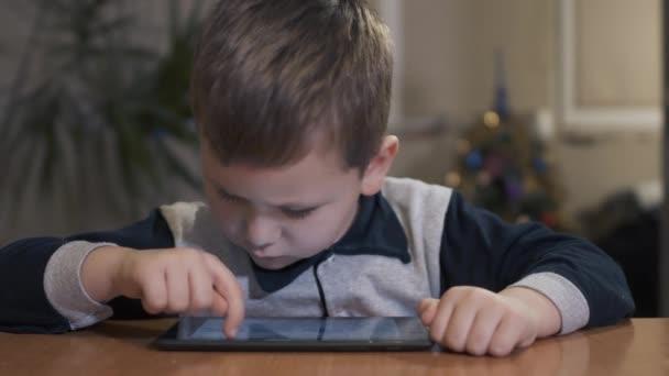 Glückliche kleine Junge arbeiten im Internet auf dem tablet