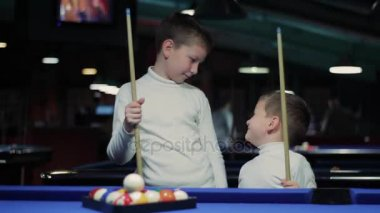 Children with cues. Boys preparing to play snooker