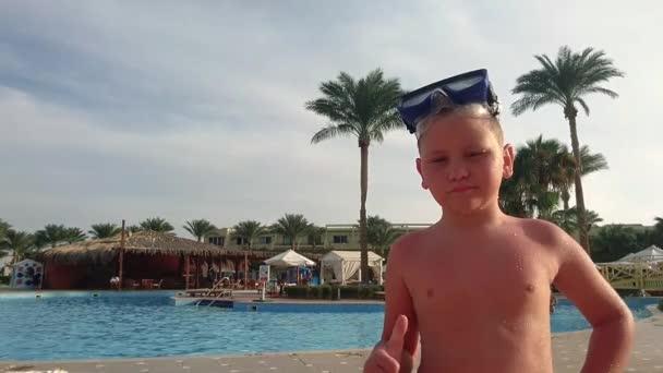 Malý mokrý chlapec stojí u bazénu