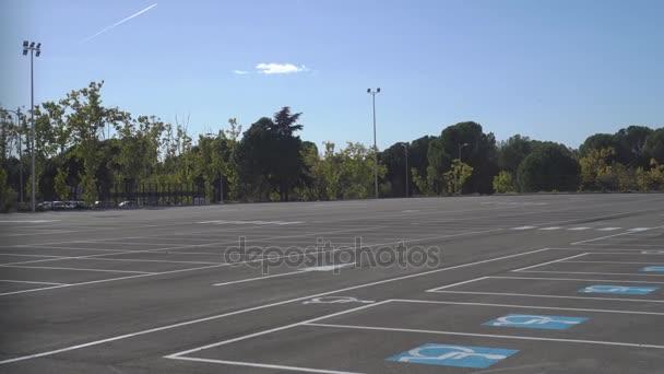 ein Blatt fällt auf den leeren Parkplatz