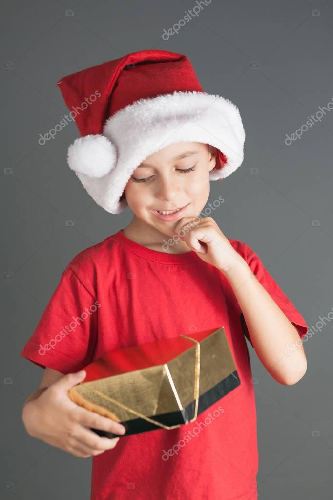 03399f1360fd3 Smiling funny child in Santa red hat holding Christmas gift in hand.  Christmas concept —