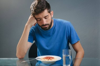 Portrait of man with no appetite in front of the meal. Concept o