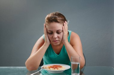 Portrait of woman with no appetite in front of the meal. Concept