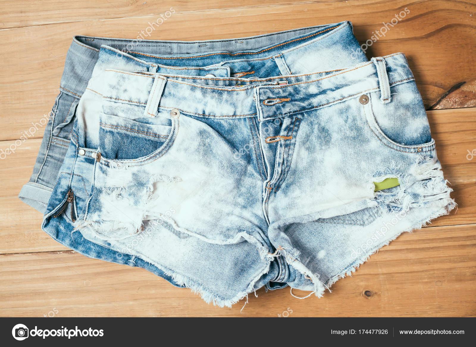 fb1b3199ce Pantalones cortos de mujer jeans rotos azul sobre fondo de madera vieja —  Foto de Stock