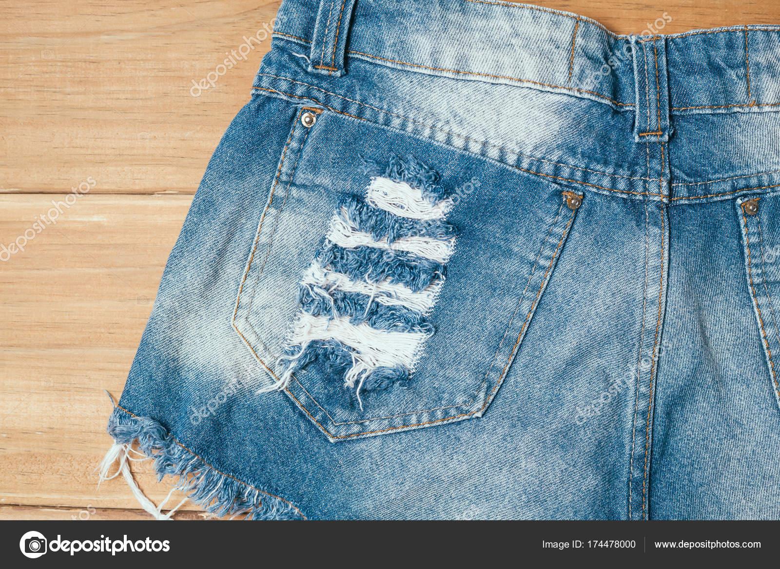 08a70a9966 Pantalones cortos de mujer jeans rotos azul sobre fondo de madera vieja —  Fotos de Stock