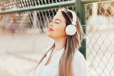 Beautiful plus-size woman listening to music in the park