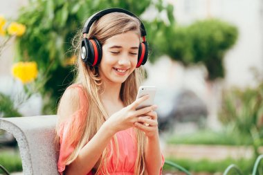 Portrait of teenager girl listening to music outdoors
