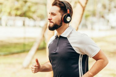 Man wearing sportswear and headphones running in park alone