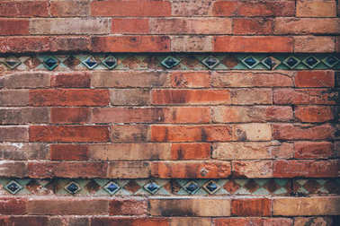 aged brick wall decorated with blue tiles for background