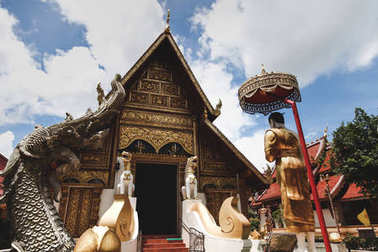 wooden thai temple with traditional hindu sculptures