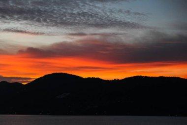 black hills silhouette under orange sunset sky