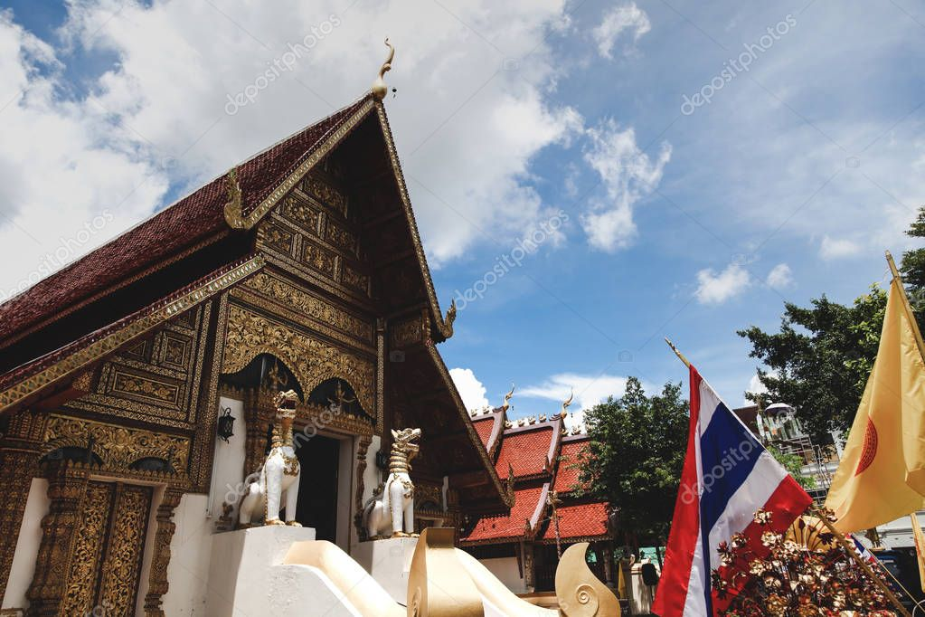 wooden thai temple with traditional hindu sculptures on sunny day