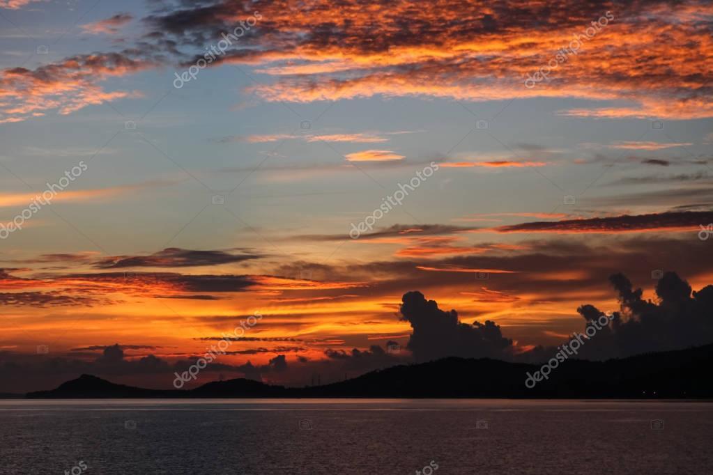 beautiful orange clouds on blue sky over evening seascape