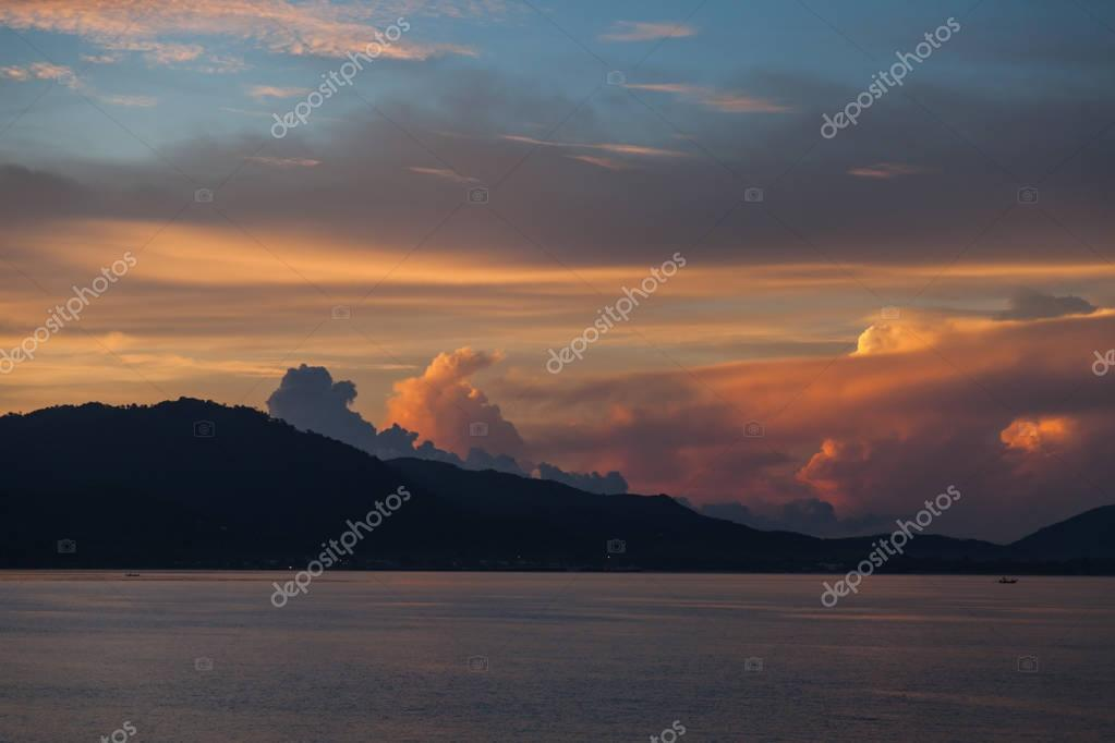 hill silhouette with dark water surface under cloudy sunset sky