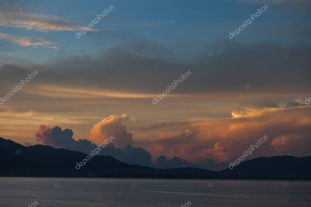 beautiful sunset cloudy sky over sea and hills