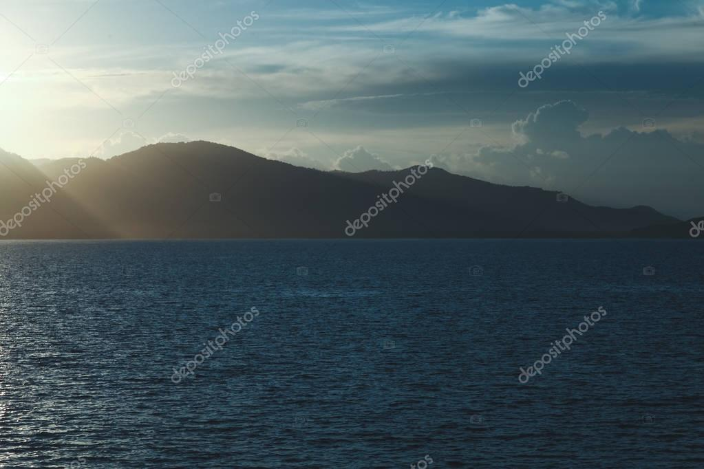 beautiful seascape with hills silhouette on evening