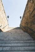 pohled zdola schodiště s zdmi a zábradlí