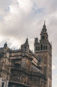 old gothic Seville Cathedral under cloudy sky, spain