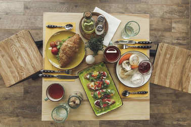 top view of tasty healthy breakfast with cheesecakes and sandwiches on table