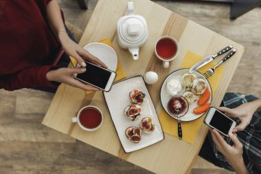 top view of people using smartphones with blank screens during breakfast