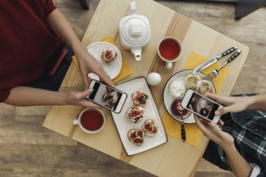 top view of people using smartphones and photographing appetizers during breakfast