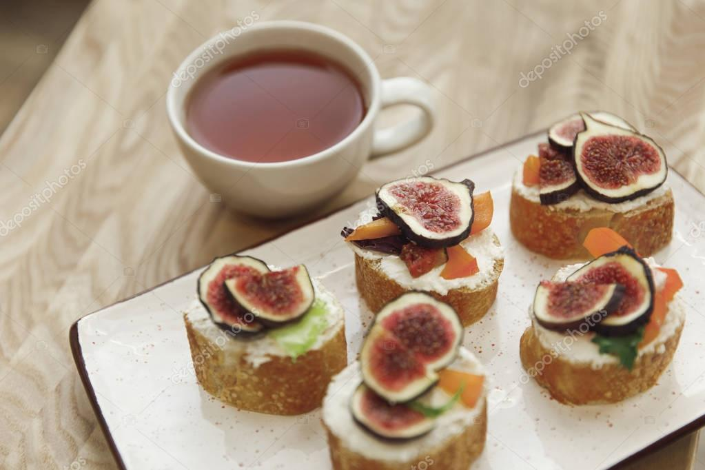 close-up view of canapes with figs and cup of tea on table