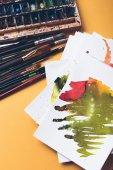 Fotografie Draufsicht der Aquarellfarben, Skizzen und Pinsel an Designer Arbeitsplatz