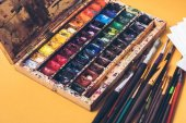 Photo close-up view of messy box of watercolor paints and paintbrushes at designer workplace