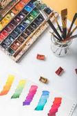 pohled shora akvarel barev, štětců a barevné malované tahy v kreslení album na návrháře pracovišti