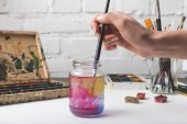 Fotografie cropped shot of artist putting paint brush into glass jar with water at workplace