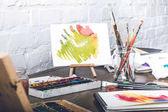 Nahaufnahme abstrakter Skizzen, Aquarellfarben und Pinsel am Designerarbeitsplatz
