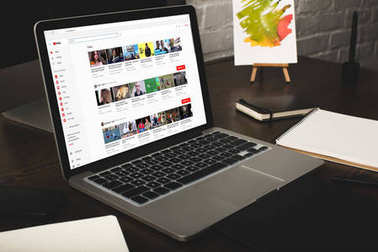 close-up view of designer workplace with notebooks and laptop with youtube website on screen