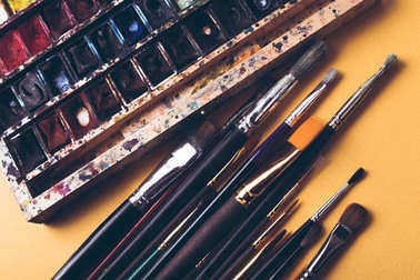 top view of paint brushes and watercolour paints at designer workplace