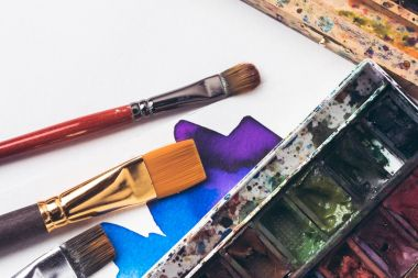 close-up view of watercolor paints and paintbrushes with drawing album at designer workplace