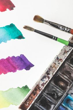 close-up view of colorful watercolor strokes in drawing album, paints and paintbrushes