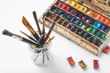 close-up view of watercolor paints and paintbrushes in glass on white