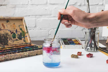 partial view of artist putting paint brush into glass jar with water at workplace