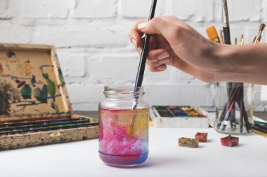 cropped shot of artist putting paint brush into glass jar with water at workplace