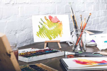 close-up view of abstract sketches, watercolor paints and paintbrushes at designer workplace