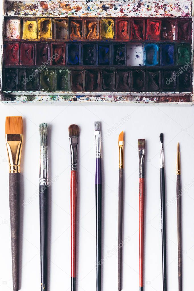 top view of well ordered paintbrushes and watercolour paints at designer workplace