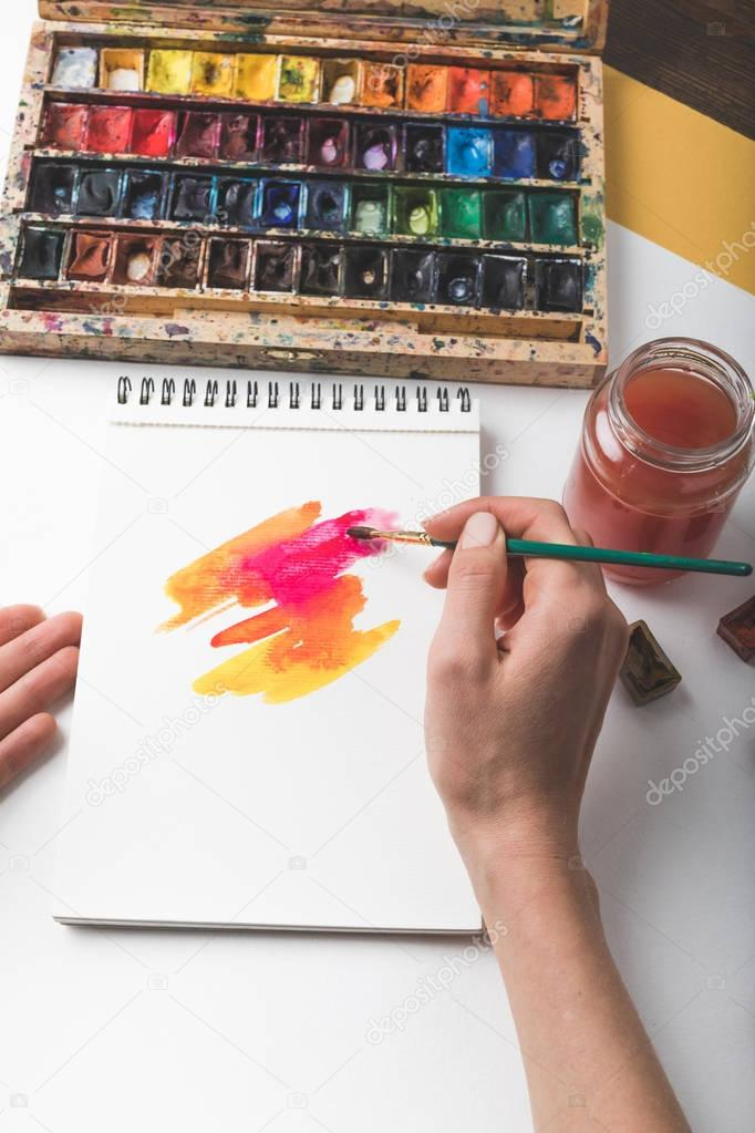 cropped shot of artist holding paint brush and drawing abstract painting